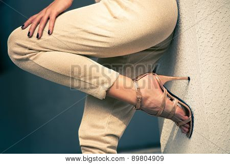 woman legs in high heel golden sandals and pants lean on wall, outdoor shot, close up