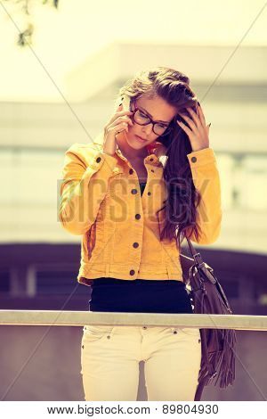 young urban woman with eyeglasses use smartphone outdoor shot in the city, retro colors