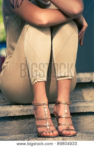 woman legs in high heel golden sandals and pants sit on stairs, outdoor shot, close up