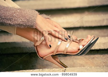 woman legs in high heel golden sandals lean on stairs, outdoor shot, close up
