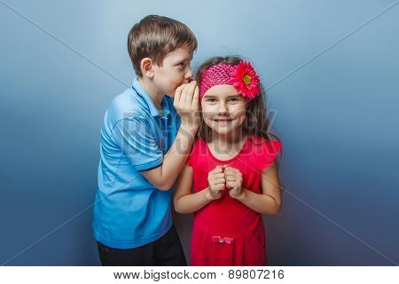 Teen boy whispering in the ear of teen girl on gray background