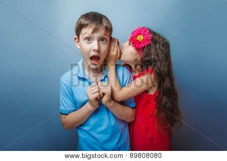 Teenage girl whispering in the ear of a secret teen  boys on a