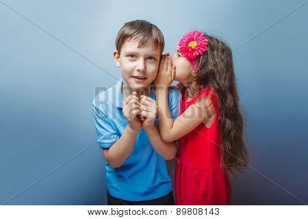 Teenage girl whispering in the ear of a secret teen boys on a gr