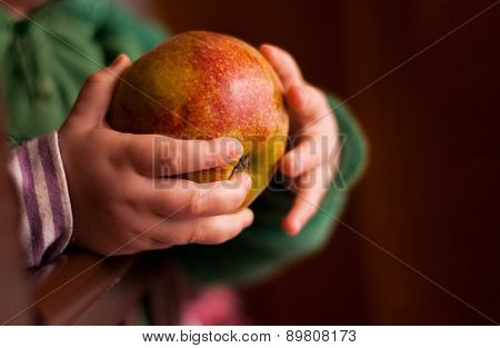 Child holding an apple in a hand