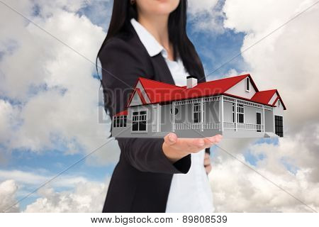Pretty businesswoman presenting with hand against blue sky with white clouds