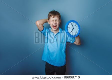 Boy teenager European appearance ten years holding wall clock op