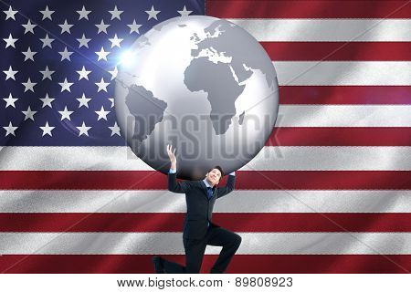 Businessman carrying the world against digitally generated american national flag