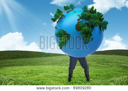 Businessman carrying the world against field and sky