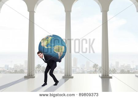 Businessman carrying the world against bright room with columns
