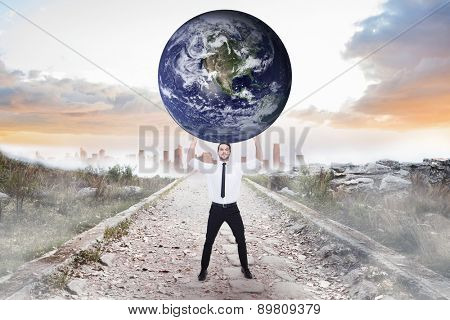 Businessman carrying the world against stony path leading to misty city horizon