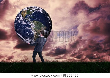 Businessman carrying the world against green grass under cloudy sky