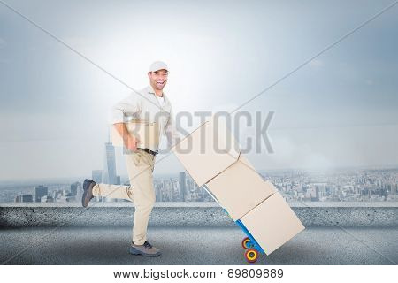 Happy delivery man with trolley of boxes running on white background against cityscape