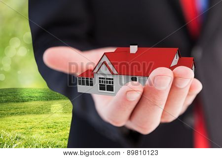 Businessman presenting with his hand against field with glowing sky
