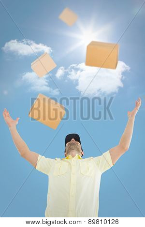 Delivery man with arms raised against bright blue sky with clouds