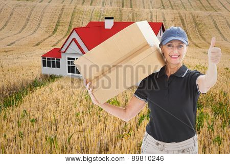 Happy delivery woman holding cardboard box against rural fields