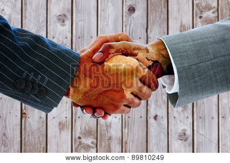 Business people shaking hands against wooden planks