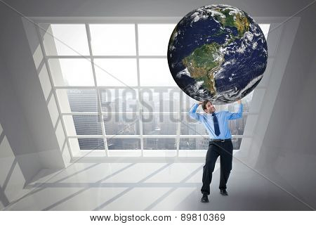 Businessman carrying the world against room overlooking city
