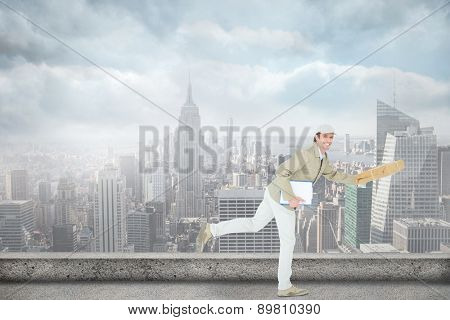 Happy delivery man running while holding parcel against cityscape