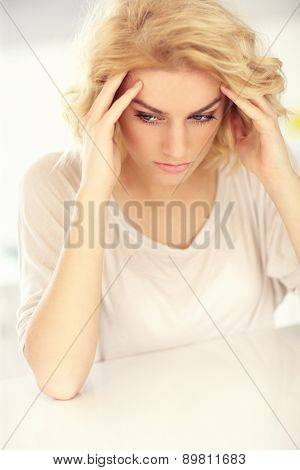 A picture of a young depressed woman with headache at home