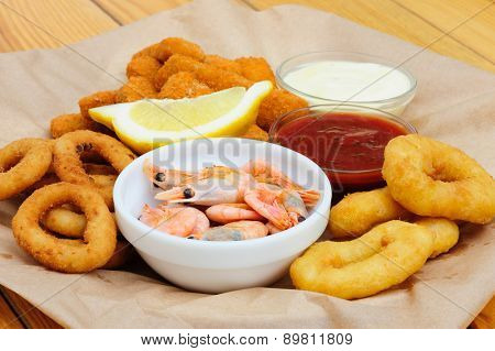 Shrimps, calmar rings and fish sticks with lemon and dip sauces, served as beer snacks