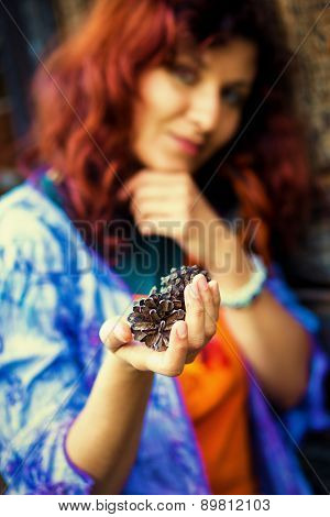 Woman Hand Holds A Fir-cone On Wood Background, Ecology Concept