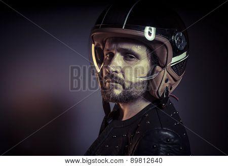 Danger, biker with motorcycle helmet and black leather jacket, metal studs