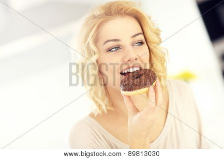 A picture of a young happy woman with donut in the kitchen
