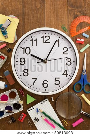 school supplies and clock on wooden background