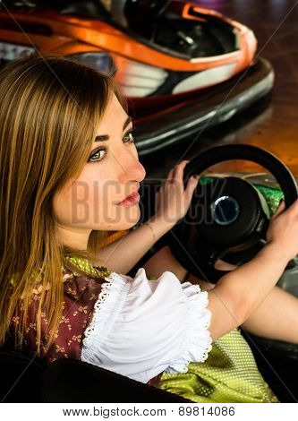 Beautiful girl in an electric bumper car in amusement park