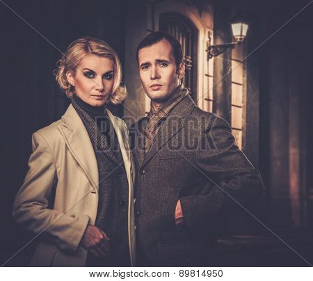 Elegant couple in autumnal coats standing outdoors at night