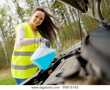 Woman adding washing fluid on a roadside