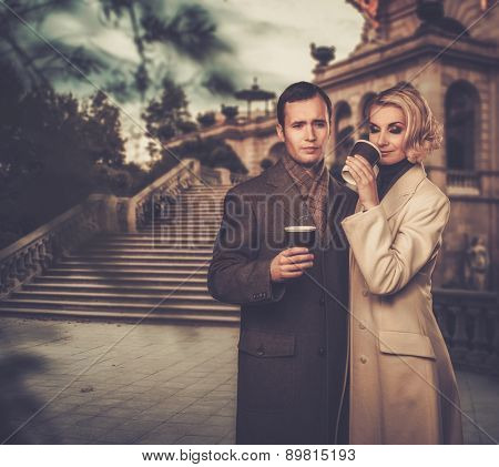 Elegant couple outdoors with cups of hot drink