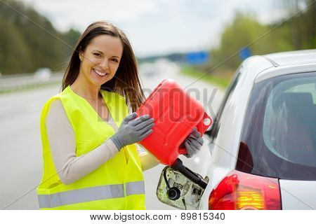 Woman refuelling her car on a highway roadside