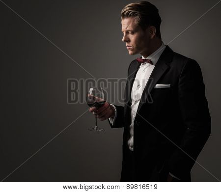 Confident sharp dressed man with glass of wine