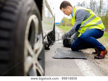 Man changing wheel on a roadside