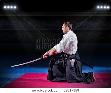 Aikido fighter with sword at sports hall