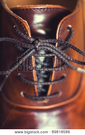 Vertical close up of laces on a brown leather business shoe