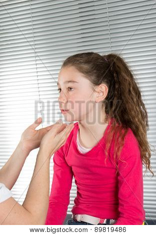 Woman Doctor Examines A Young Girl's Throat