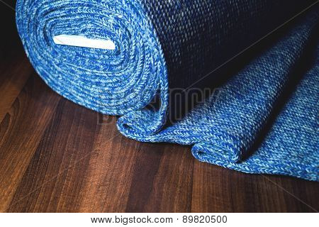 Blue fabric roll on wooden background