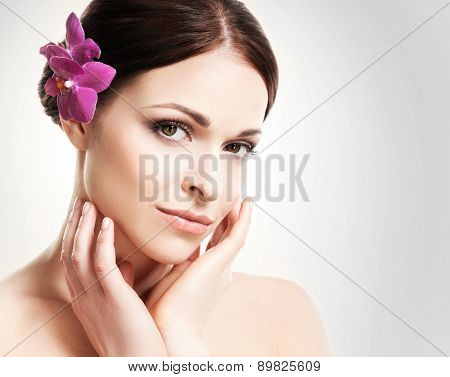 Beautiful face of a young and healthy girl with an orchid flower in her hair over grey background