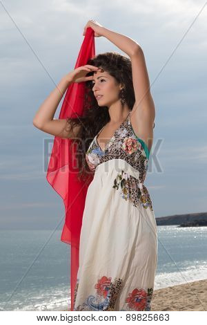 Attractive young woman on the beach waving with a red chiffon scarf