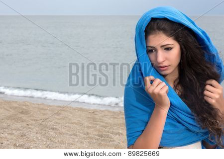 Windy day on the beach with a girl wrapped in a blue headscarf