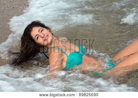 Young attractive woman lying on the beach enjoying the waves