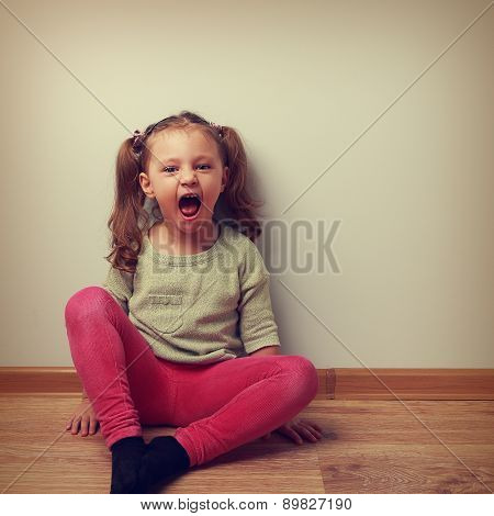 Happy Crying Kid With Open Mouth Sitting On The Floor. Vintage