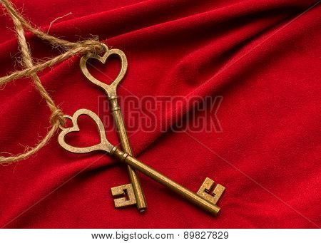 Two vintage key in the form of heart on a red fabric