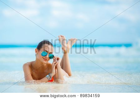 Young female enjoying sunny day on tropical beach.