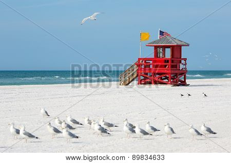 Red wooden lifeguard hut on an empty beach