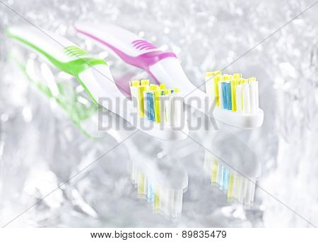 Two Tooth Brushes On Bright Background.