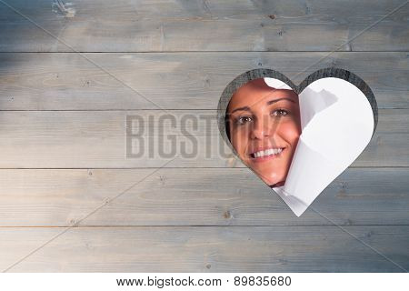 Young couple looking through paper rip against heart in wood
