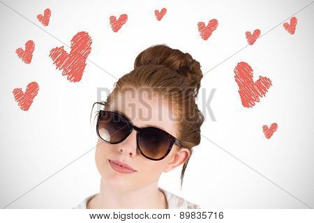 Hipster redhead wearing large sunglasses against white background with vignette